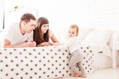 Les parents enseignent l'enfant à s'élever sur le lit Photographie stock