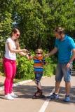 Les parents enseignent le petit fils à monter sur des patins de rouleau Photo libre de droits