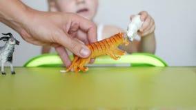 Les parents enseignent un petit enfant à distinguer les animaux, un jeu du ` s d'enfant avec des jouets et les parents, plan rapp clips vidéos
