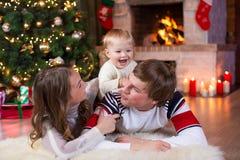 Les parents et l'enfant heureux ont un amusement près de l'arbre de Noël à la maison Père, mère et fils célébrant la nouvelle ann Photographie stock
