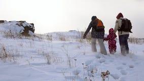 Les parents et un enfant marchent le long d'un chemin couvert de neige vers le haut banque de vidéos