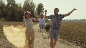 Les parents gais soulèvent leur enfant, alors qu'il vient par l'air se dandinant ses jambes banque de vidéos