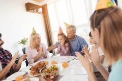 Les parents, les grands-parents et le frère félicitent la petite fille sur son anniversaire Images libres de droits
