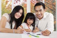 Les parents heureux aident leur étude d'enfant photos libres de droits