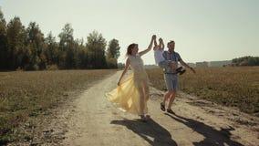 Les parents joyeux soulèvent leur fils tout en courant le long de la route de campagne clips vidéos