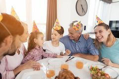 Les parents, le frère et la grand-mère avec le grand-père félicitent la fille sur son anniversaire se reposant à la table de fête Image stock
