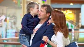 Les parents parlent au fils dans le mail commercial La famille a fait des achats pour Noël au centre commercial Noël banque de vidéos