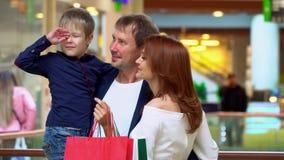 Les parents parlent au fils dans le mail commercial La famille a fait des achats pour Noël au centre commercial Parents gais banque de vidéos