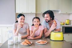 Les parents se penchent pour ajourner avec leur fille Le type regarde la petite fille Elle et sa mère mangent des petits pains images stock