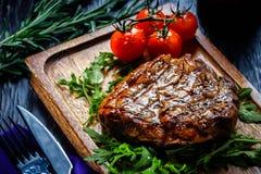 Les parties juteuses de filet grillé ont servi avec des tomates et photographie stock libre de droits