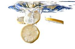 Les parts de citron tombent dans l'eau Images libres de droits