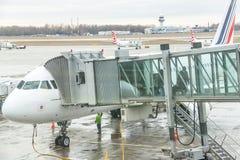 Les passagers d'aéroport sont sortent de l'avion à la porte terminale Photos stock