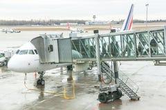 Les passagers d'aéroport sont sortent de l'avion à la porte terminale Photo libre de droits