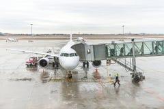 Les passagers d'aéroport sont sortent de l'avion à la porte terminale Photo stock