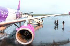 Les passagers d'aéroport sont sortent de l'avion Photographie stock
