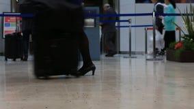 Les passagers de voyageurs dans l'aéroport transitent le terminal marchant avec le déplacement allant de bagages de bagage clips vidéos
