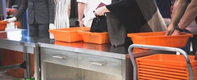 Les passagers font la queue sur la ligne pour les sacs de balayage images stock