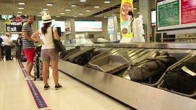 Les passagers larges de tir attendent leur bagage au retrait des bagages après un vol international en Asie banque de vidéos