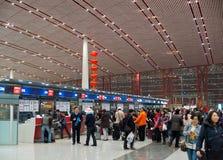 Les passagers se tiennent dans les files d'attente pour signer des compteurs à l'airpo de Pékin Photos stock