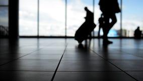 Les passagers suivent à l'embarquement avec des bagages devant la fenêtre dans l'aéroport, silhouette banque de vidéos