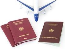 Les passeports allemands de famille avec l'avion ont isolé le fond blanc Photo stock