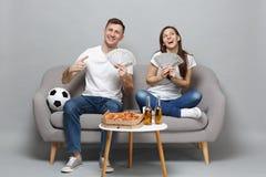 Les passionés du football d'homme de femme de couples de Dreamful encouragent l'équipe de favori de soutien tenant la fan de l'ar photos libres de droits