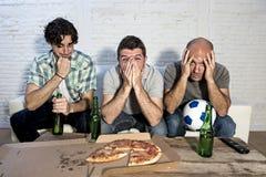 Les passionés du football fanatiques d'amis regardant la TV s'assortissent avec l'effort de douleur de bouteilles et de pizza à b Photographie stock libre de droits