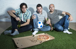 Les passionés du football fanatiques d'amis regardant la TV s'assortissent avec l'effort de douleur de bouteilles et de pizza à b Image libre de droits