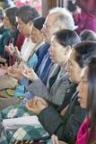 Les passionnés tiennent les perles de prière et le riz pendant une cérémonie bouddhiste d'habilitation d'Amitabha, bâti de médita Image stock