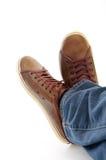 Les pattes dans le brun chausse des espadrilles se trouvant vers le bas d'isolement Images stock