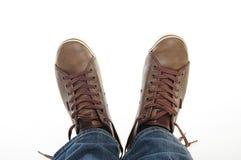 Les pattes dans le brun chausse le mensonge d'espadrilles et de jeans Image libre de droits