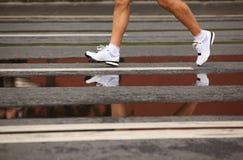 Les pattes de l'homme courant dans des chaussures courantes sur l'asphalte Image libre de droits