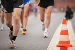 Les pattes de l'homme de Runing près du cône de couleur sur l'asphalte Photo stock