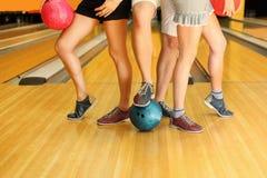 Les pattes de l'homme et des filles avec des billes dans le bowling matraquent Image libre de droits