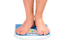 Les pattes de l'homme, pesées sur l'échelle d'étage. Image libre de droits