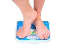 Les pattes de l'homme, pesées sur l'échelle d'étage. Photo libre de droits