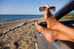 Les pattes de la femme balançant à l'extérieur un hublot de véhicule Photographie stock