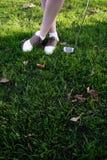 Les pattes de Madame dans des chaussures de golf Photographie stock