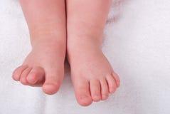 Les pattes des enfants sur un essuie-main mol Photographie stock libre de droits