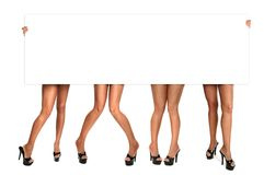 Les pattes des femmes retardant un signe blanc Photographie stock