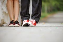 Les pattes des nouveaux mariés dans des espadrilles Photographie stock