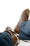Les pattes mâles dans le brun chausse des espadrilles et des jeans Photographie stock libre de droits