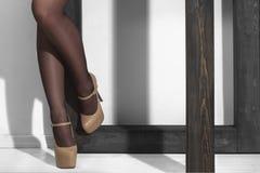 Les pattes sexy dans de hauts talons s'approchent du pôle Images stock