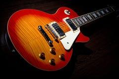 Les Paul guitar. Cherry sunburst Les Paul guitar on dark  brown wooden floor Royalty Free Stock Photos