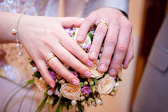 Les paumes des jeunes mariés sur le bouquet Image libre de droits