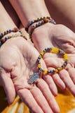 Les paumes femelles avec la perle naturelle lapident des bracelets tenant le bracelet avec le pendant photographie stock libre de droits