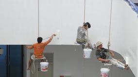Les peintres peignent sur de hauts bâtiments avec la grande corde banque de vidéos
