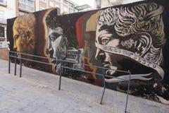 Les peintures des singeries fait face à des statues sur un mur images stock