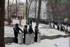 Les pelotons de police se cachent dans le parc et attendent l'ordre à l'attackon sur la rue de occupation de neige pendant l'émeut Images libres de droits