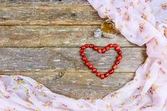 Les perles en bois rouges ont présenté la forme d'un coeur sur une vieille table en bois Images libres de droits